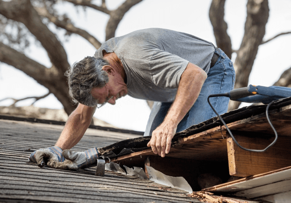 Man Repairing The Roof Of His House